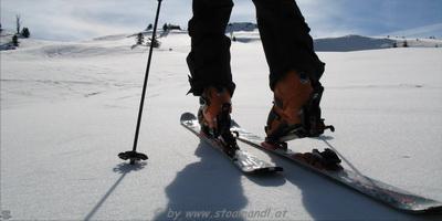 Vier Skitourengeher machen eine Pause bei einer Tages-Skitour.
