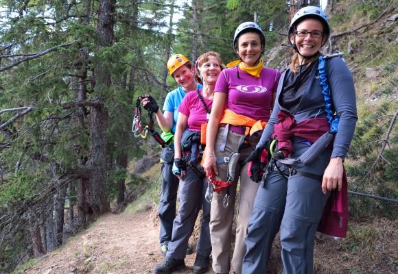 Kletterin lächelt in der Felswand beim Klettern im Tirol.