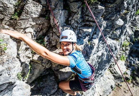 Der Guide hilft der Kletterin beim Anlegen der Ausrüstung beim Tageskletterkurs.
