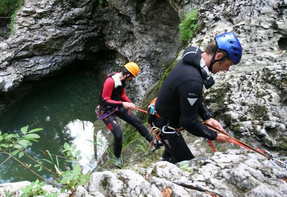 Der Sportler seilt sich am Wasserfall ab beim Canyoning.