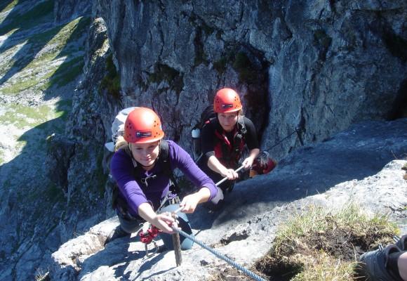 Die Kletterer gehen am Seil immer weiter nach oben am Klettersteig.