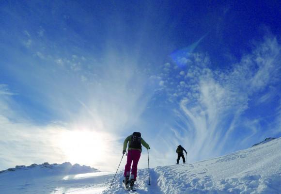 Vier Tourengeher halten ihre Skistöcke nach oben bei einer Tages-Skitour.