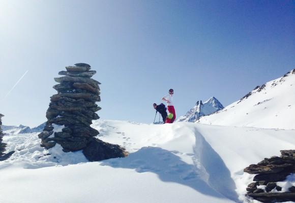 Zwei Skitourengeher am Gipfelkreuz bei strahlendem Sonnenschein bei der Skitour Sellrain I.