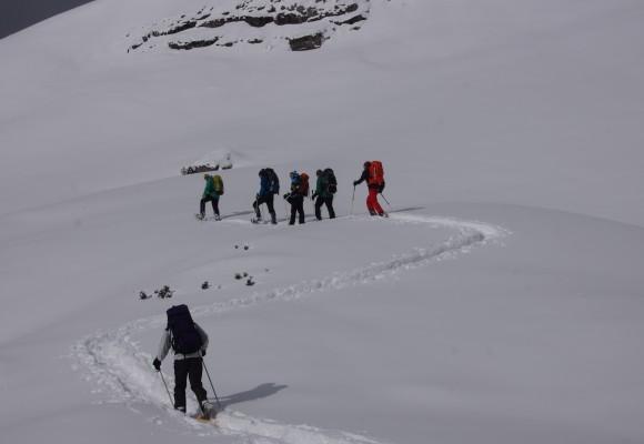 Schneeschuhwandergruppe vor dem Gipfelkreuz.