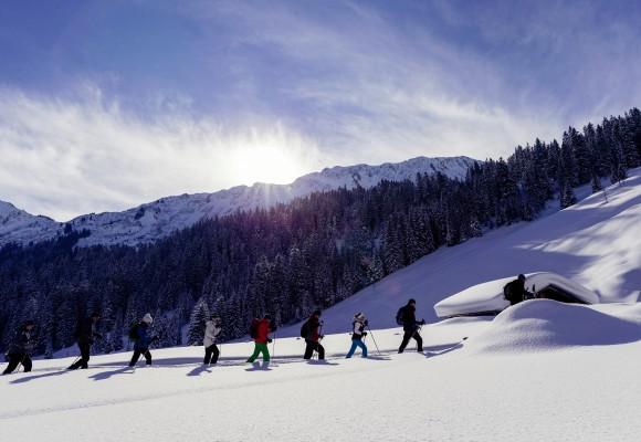 """Schneeschuhwanderer liegt im Schnee bei der Tour """"Unterwegs im Steigbachtal"""""""