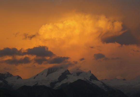 Bergsteiger auf imposantem Gipfel im Sonnenschein.