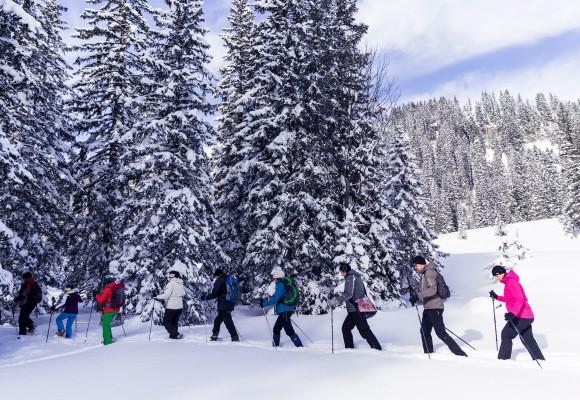 Schneeschuhwanderer pausieren und setzen sich in den Schnee.